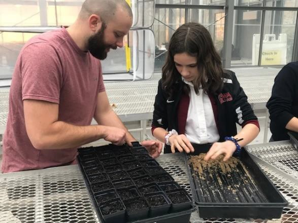 Dr. Joshua Puzey, Assistant Professor at the College of William & Mary, assists Alyson Pellei in preparing and planting milkweed seeds.