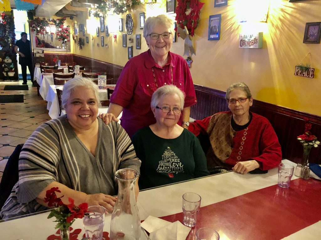"""CAPTION: Four women on a mission. Maria Guadalupe """"Lupita"""" Martinez (left) founded the CREA adult learning center in conjunction with the Mexican Consulate in New York City in 2013. Sister Suzanne (center), Dorothy Calvani (standing) and Dava Weinstein (right) serve on CREA's board and work closely with Lupita to help the center offer not only literacy classes, but also workshops on subjects ranging from leadership and self-esteem to running a business. During the pandemic, the women and other board members have been in constant touch by phone and have participated in Zoom board meetings. (Catherine Walsh photo)"""