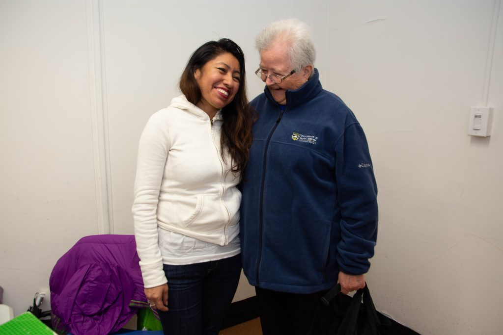 """CAPTION: Sharing a laugh with a student. In her CREA board of directors' profile, Sister Suzanne, age 82,  calls her ministry with East Harlem's people """"the most treasured part"""" of her life. She also notes that her passions include not only immigration, the climate and racism, but also """"wherever we find injustice, hatred and devastation, wherever families cannot live life."""" The nun threw a CREA fundraiser for her 80th birthday in 2018 and is grateful for financial support provided to CREA by the Northeast Ministry Fund of the Sisters of Mercy. (Catherine Walsh photo)"""