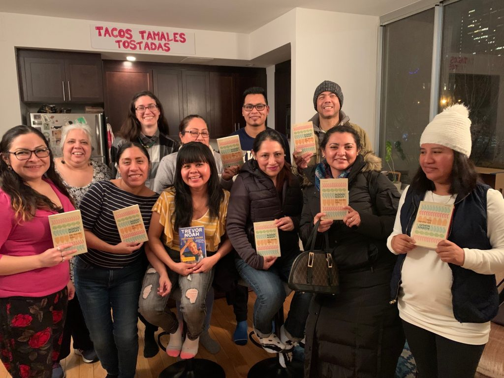 CAPTION: The joy of a good book club. Before coronavirus closed New York City, the CREA Reading Club met at the home of Paulina Concha, CREA's president and board chairperson (standing, back row). Other CREA staff include Lupita Martinez (second row, far left), CREA's founder. The young man wearing glasses, in the second row, came to CREA knowing no English and is now in college. The CREA Reading Club has been meeting by Zoom video during the pandemic. (CREA photo)