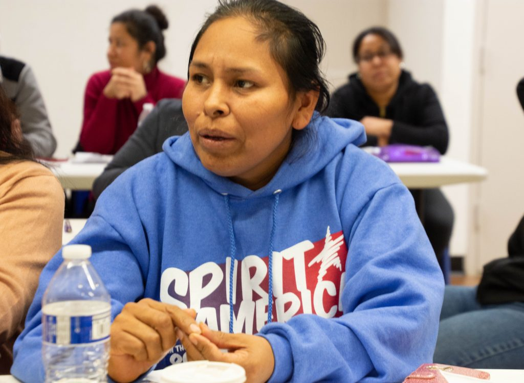 """CAPTION: Each of CREA's nearly 160 adult students, like this woman, learn first-hand that their new skills get them better jobs, make them more effective parents, and help them contribute to the community. """"When students come to us, they don't know they are very talented people,"""" says founder Lupita Martinez. """"It's amazing to see them grow."""" Lupita, Sister Suzanne and CREA's other supporters believe that the """"Spirit of America""""—in the words of this student's jersey—is about helping each other reach our potential and fulfill our nation's ideals. (Catherine Walsh photo)"""