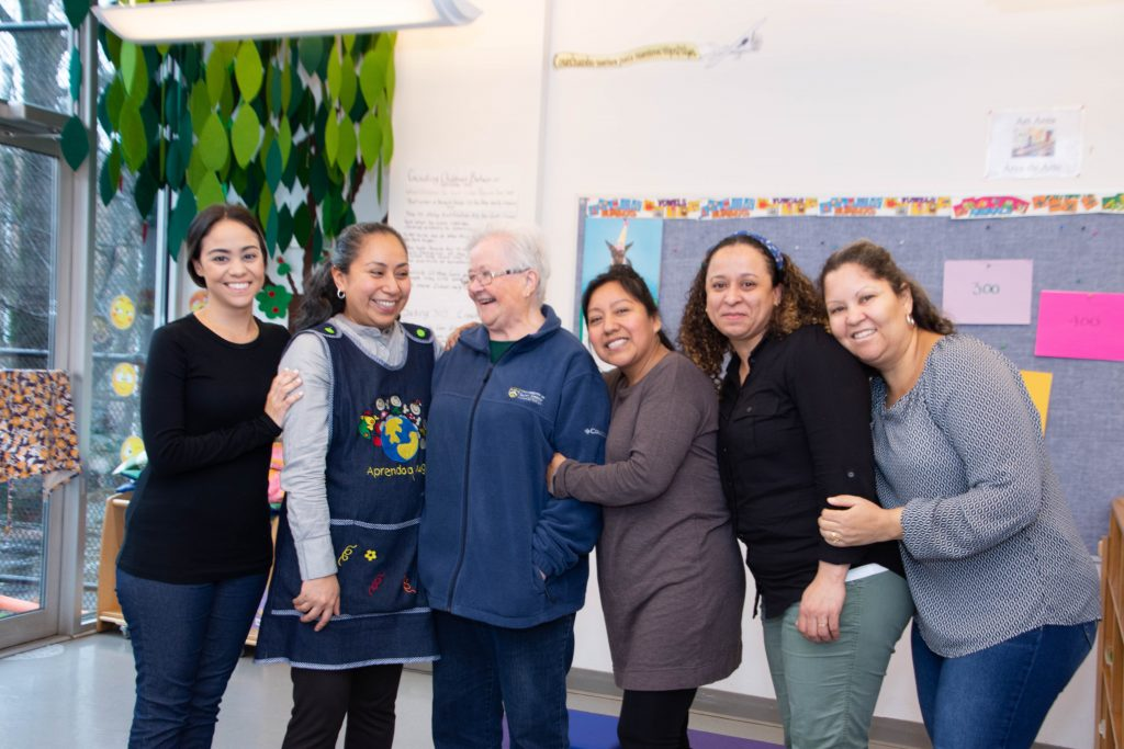 """CAPTION: Bonds forged before the pandemic allow Sister Suzanne and LSA Family Health Service staff—many of them immigrants—to work well together remotely. (From left) Thangi Garcia, Wendy Mejia, Sister Suzanne, Yolanda Otero, Maria Ramirez and Elva Torres. Noted Reada Bunin Edelstein, the agency's CEO, """"Foundations that support us don't know of another agency where people feel so welcome and safe. The degree of trust is unusual and it's due to our staff and people like Sister Suzanne, who is so loved and deeply trusted in the community."""" (Catherine Walsh photo)"""
