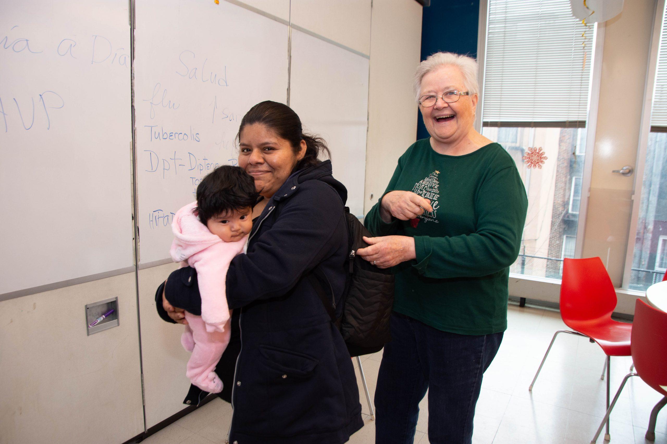 """Compartiendo un momento de alegría en el Servicio de Salud Familiar de LSA, donde la Hermana Suzanne dicta clases como la de Día a día con tu bebé (""""Day by Day with Your Baby""""). Antes de «retirarse» hace cinco años y de convertirse en voluntaria, la Hermana Suzanne subió innumerables tramos de escalera en las viviendas de East Harlem durante más de 20 años, ayudando a las nuevas madres a cuidar de sus hijos. Como Hermana de la Misericordia trabajó durante trece años en Nicaragua al lado de la Congregación de Hermanas Dominicas de Maryknoll, y en 1993 regresó a su casa para cuidar a su padre y buscar un trabajo con inmigrantes latinoamericanos. Una amiga le habló sobre LSA y allí ha permanecido desde entonces. (Foto de Catherine Walsh)"""