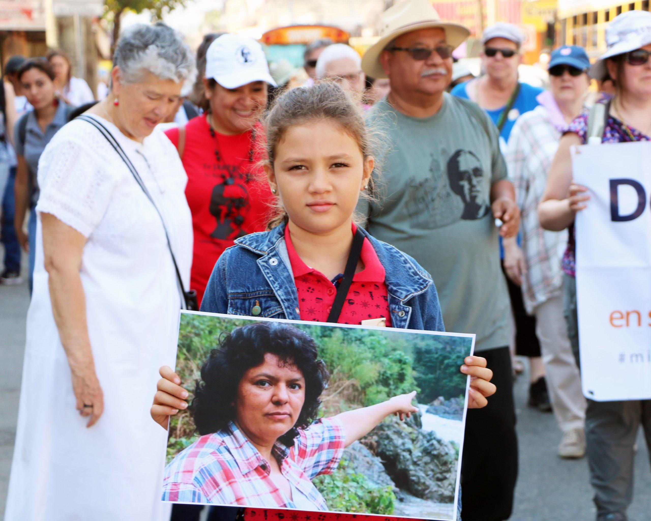 Una niña porta una foto de Berta Cáceres durante una manifestación.