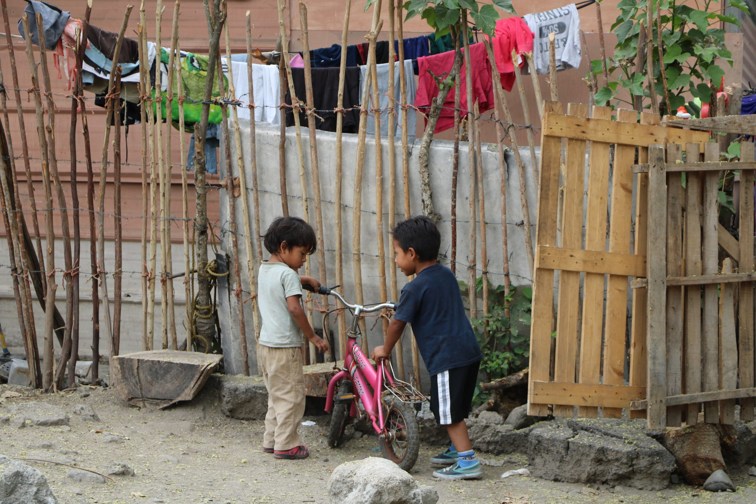 Two Honduran children play together outside of their home.