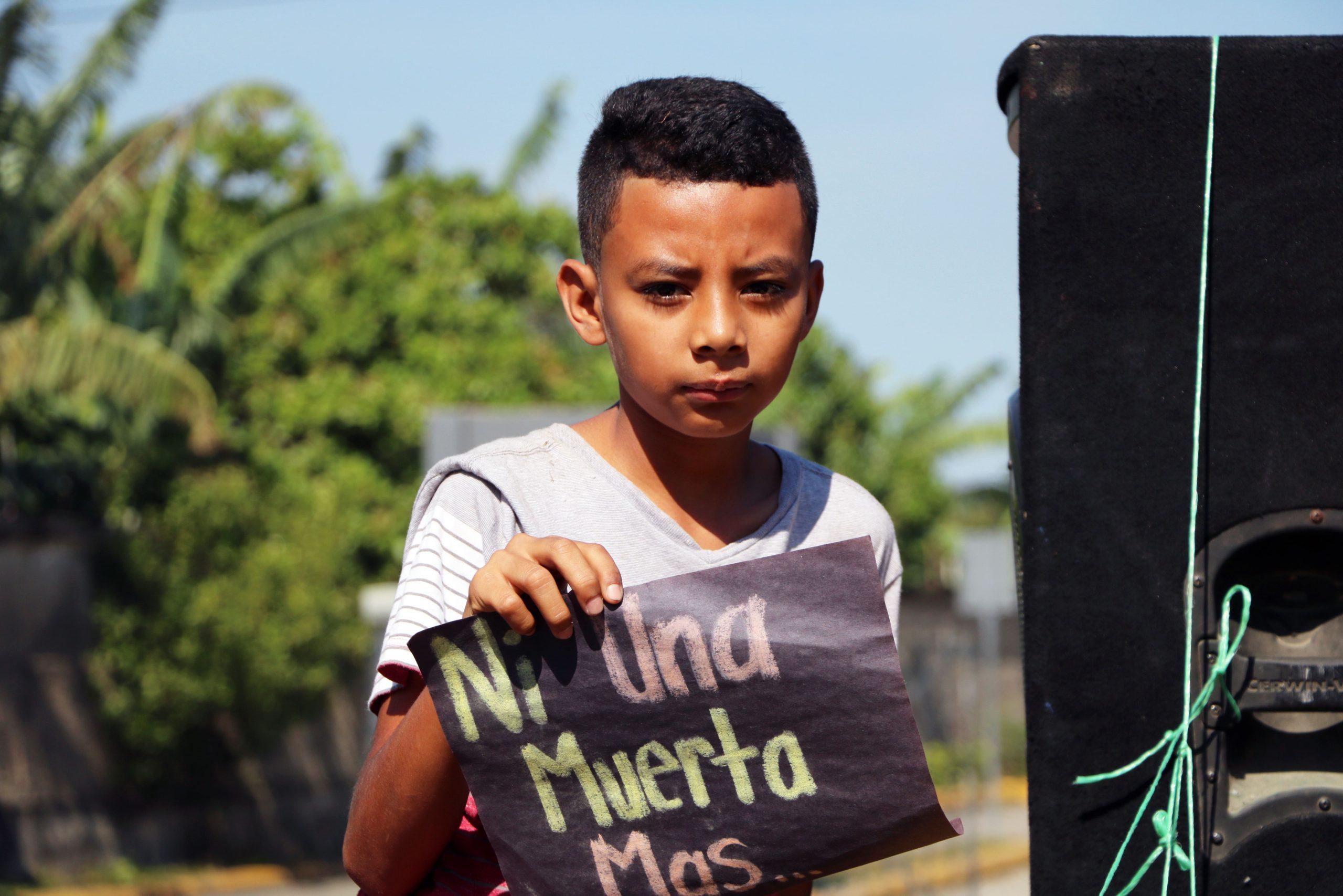 Un niño sostiene su mensaje durante una manifestación.